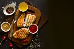 Grilled chicken breasts with spices on wooden desk Royalty Free Stock Photos