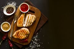 Grilled chicken breasts with spices on wooden desk. Top view. Space for copy. Toned image Royalty Free Stock Photography