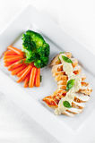 Grilled Chicken Brest with Veggies. A juicy chicken breast grilled and topped with alfredo sauce and steamed carrots and broccoli as side dish Stock Image