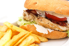 Grilled chicken burger with chips on white plate. Royalty Free Stock Images