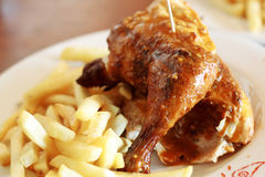 Grilled chicken and chips. Half grilled chicken and some deep fried chips on a plate Royalty Free Stock Photo