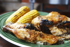 Grilled chicken with corn cobs on background Stock Images