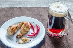 Grilled chicken drumsticks with a mug of beer Royalty Free Stock Photo