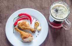 Grilled chicken drumsticks with a mug of beer Royalty Free Stock Image