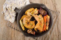 Grilled chicken drumsticks with vegetable in a cast iron pan Stock Photo