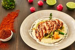 Grilled chicken fillet is cut into slices on a cushion of mashed potatoes with vegetables - onion, garlic, pepper, cabbage, radish. Greens in a large beige Stock Images