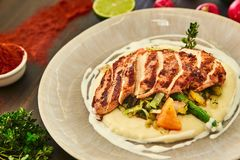 Grilled chicken fillet is cut into slices on a cushion of mashed potatoes with vegetables - onion, garlic, pepper, cabbage, radish. Greens in a large beige Royalty Free Stock Photos