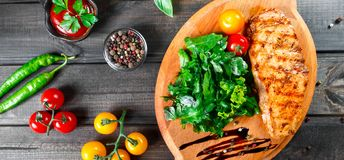 Grilled chicken fillet with fresh vegetable salad, tomatoes and sauce on wooden cutting board. Grilled chicken fillet with fresh vegetable salad, tomatoes and stock image