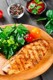 Grilled chicken fillet with fresh vegetable salad, tomatoes and sauce on wooden cutting board.  stock photos