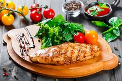Grilled chicken fillet with fresh vegetable salad, tomatoes and sauce on wooden cutting board.  royalty free stock photography