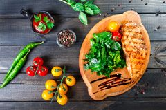 Grilled chicken fillet with fresh vegetable salad, tomatoes and sauce on wooden cutting board. Hot Meat Dishes. Top view stock image