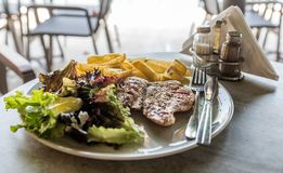 Grilled chicken fillet with fried potato, Iceberg salad and vegetables stock image