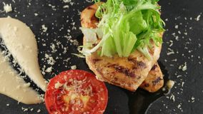 Grilled chicken fillet with sauce. On black slate tray stock footage