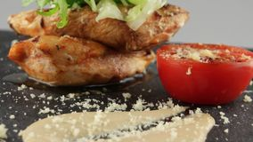 Grilled chicken fillet with sauce. On black slate tray stock video
