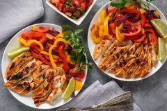 Grilled chicken fillet with sauteed peppers and onion. stock images