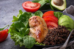 Grilled chicken fillet with vegetable and quinoa. Grilled chicken fillet with black quinoa, salad, tomatoes and avocado. Healthy balanced food Stock Photos