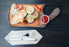 Grilled chicken fillet with vegetables and sauce on a wooden board. top view stock images