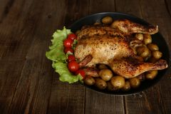 Grilled chicken with a golden crust and potatoes in a pan, decorated with green lettuce leaves and small red tomatoes on a wooden royalty free stock image