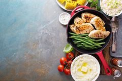 Grilled chicken with green beans in a skillet. Big summer dinner with grilled chicken, green beans , corn on cob and mashed potatoes overhead shot with copy royalty free stock image