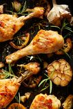 Grilled chicken. Grilled chicken legs, drumsticks with addition, garlic, lemon and rosemary on grill plate, top view. royalty free stock images