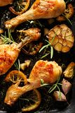 Grilled chicken. Grilled chicken legs, drumsticks with addition, garlic, lemon and rosemary on grill plate, top view. Grilled chicken. Grilled chicken legs royalty free stock photo