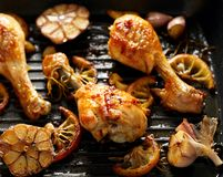 Grilled chicken. Grilled chicken legs, drumsticks with addition, garlic, lemon and rosemary on grill plate, top view. royalty free stock photo