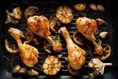 Grilled chicken. Grilled chicken legs, drumsticks with addition, garlic, lemon and rosemary on grill plate, top view. stock photography