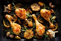 Grilled chicken. Grilled chicken legs, drumsticks with addition, garlic, lemon and rosemary on grill plate, top view. stock photo