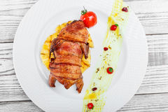 Grilled chicken in a ham with pineapple and tomatoes on plate on wooden background close up Royalty Free Stock Photos