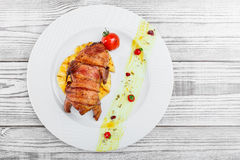 Grilled chicken in a ham with pineapple and tomatoes on plate on Stock Image
