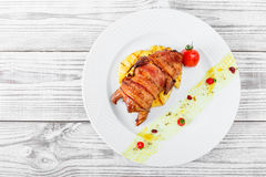 Grilled chicken in a ham with pineapple and tomatoes on plate on wooden background Royalty Free Stock Photo