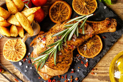 Grilled chicken leg, French fries and orange royalty free stock image