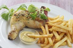 Grilled chicken leg and french fries with salad Stock Photo