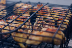 Grilled chicken Leg on the grill, over coals with smoke Royalty Free Stock Photo