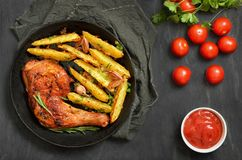 Grilled chicken leg with herbs and fried potatoes. In frying pan, top view royalty free stock photography