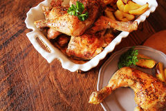 Grilled chicken leg with potato for garnish. Top view. Wooden background. Royalty Free Stock Photo