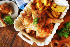 Grilled chicken leg with potato for garnish. Top view. Wooden background. Stock Image