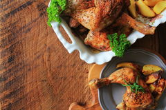 Grilled chicken leg with potato for garnish. Top view. Wooden background. Stock Photos