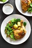 Grilled chicken leg with potato and green salad. On black stone background. Dish for dinner. Top view, flat lay stock photography