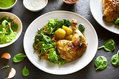 Grilled chicken leg with potato and green salad. On black stone table. Tasty dish for dinner royalty free stock images