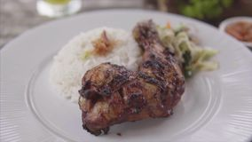 Grilled chicken leg with steamed rice at the restaurant. Plate with chicken, rice served on the wooden table with stock footage
