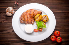 Grilled chicken leg with vegatables and seasoning on a wooden ba Royalty Free Stock Photos