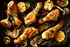 Grilled chicken legs with addition of aromatic rosemary, garlic, onion, leek and spices on a grill plate royalty free stock photo