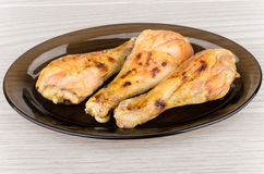 Grilled chicken legs in black dish on table Royalty Free Stock Photography
