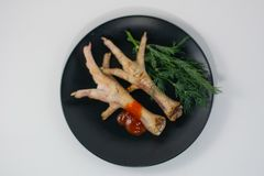 Grilled chicken legs on a black plate stock image
