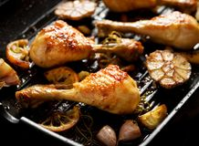 Grilled chicken. Grilled chicken legs, drumsticks with addition, garlic, lemon and rosemary on grill plate, top view. Grilled chicken. Grilled chicken legs stock photos