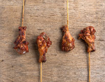 Grilled chicken legs skewer on old wood textured background. From thailand Stock Photo