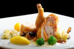 Grilled chicken legs with stuffed pork tenderloin roulade. Garnished with sweet potato gnocchi, truffles  and vegetables Royalty Free Stock Images