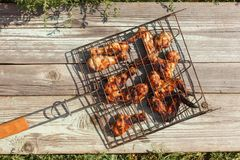 Grilled chicken Legs and wings on the grate. On the wooden background. Concept of family family holiday, rustic style Stock Photos