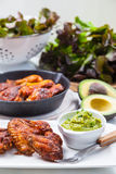 Grilled chicken legs and wings with guacamole Stock Images